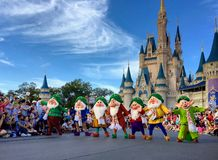Seven dwarfs performancing at Walt Disney World Christmas party. Crowd watching seven dwarfs singing and dancing in front of Cinderella Castle at Christmas Royalty Free Stock Photos