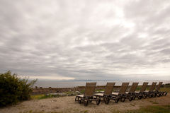 Seven Empty Beach Recliner Chairs on a Cloudy Morning Stock Photography