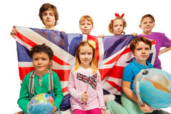 Seven English kids studying geography with globes. Seven happy English kids studying geography with globes and holding flag of Great Britain, isolated on white stock photography