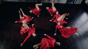 Seven female dancers are lying on a floor in round figure, moving and standing up, top view on their bodies