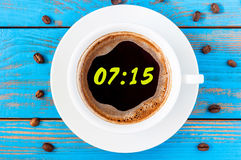 Seven fifteen hours or 7:15 on morning cup of coffee like a round clock face. Top view on blue wooden background Royalty Free Stock Photo