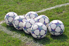 Seven football balls lying on the grass Royalty Free Stock Photo