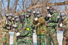Friends in masks and camouflage play paintball Stock Photos