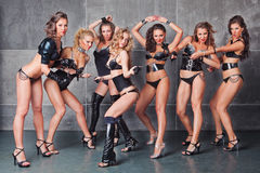 Seven go-go girls in black with diamonds costume. Seven Cute go-go sexy girls in black with diamonds costume pulling a chain Royalty Free Stock Photos