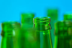 Seven green bottle necks on blue background Stock Photography