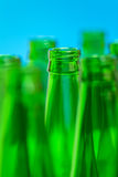 Seven green bottle necks on blue background. Stock Photos