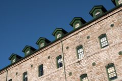 Seven Green Windows. Seven green attic windows atop an old stone industrial building royalty free stock photography