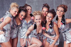 Seven happy smiling cute girls in silver go-go. Group of seven happy smiling cute girls in silver go-go costume ready to party Stock Photos