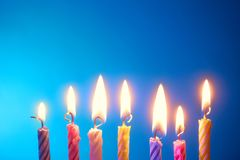 Seven Holiday candles. Holiday - birthday candles in a row over blue background Stock Photography