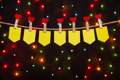 Seven holiday flags  with hearts. On the background of colored lights Stock Images