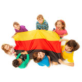Seven kids holding German flag sitting around it. Top view of seven happy kids holding German flag sitting around it, isolated on white background stock photo
