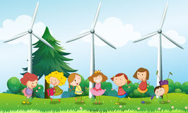 Seven kids playing in the hill with three windmills Royalty Free Stock Image