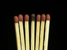 Seven matches. On black background – one is burned royalty free stock image