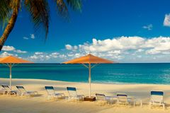 Seven Mile Beach-Parasols And Sun Loungers. Parasols and sun loungers facing the Caribbean Sea on Seven Mile Beach, Grand Cayman, Cayman Islands stock photos