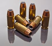 Seven 9mm hollow point bullets. With their reflections together on a glass surface Stock Images