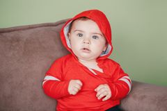 Seven months child sitting on couch at home looking in camera Royalty Free Stock Photos