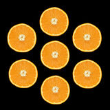 Seven Orange Slices. Seven slices of orange in a circular pattern on a black background royalty free stock photos