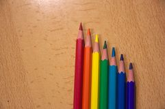 Seven pencils over a table. Some pencils of the seven colors of the rainbow to paint Stock Photos