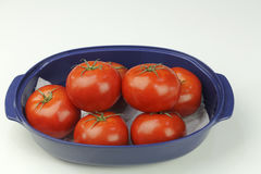 Seven Red Tomatoes in a Blue Bowl. Many hydroponically grown red tomatoes grouped in an oblong blue bowl on a white quartz kitchen counter up close. Several red Royalty Free Stock Photos