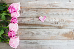 Seven roses on wooden background. Seven pink and blush roses on wooden background Royalty Free Stock Photos