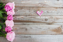 Seven roses on wooden background. Seven pink and blush roses on wooden background Stock Photos