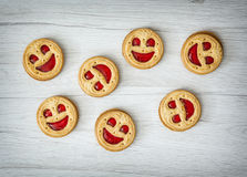 Seven round biscuits smiling faces, humorous food Stock Images