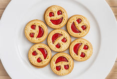 Seven round biscuits smiling faces on the white plate Stock Images