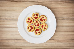 Seven round biscuits smiling faces on the white plate, humorous Royalty Free Stock Photo