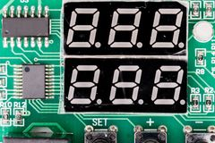 Seven-segment display SSD, or indicator, electronic display device for displaying decimal numerals. On green pcb with controller royalty free stock photo