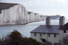 Seven Sisters chalk cliffs. Scenic view of Seven Sister chalk cliffs with coastguard cottages in foreground, South Downs, East Sussex, England Stock Image