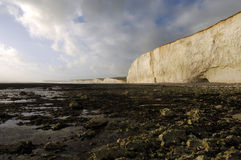 Seven Sisters Cliffs. White cliffs, rocky shore, blue sky and clouds, Seven Sisters, Birlin Gap, south coast of UK Stock Images