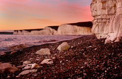 Seven Sisters Cliffs at Dusk. Eastbourne UK. Pink red sky at Birling Gap near Eastbourne UK. The white chalk cliffs known as the Seven Sisters in the distance Royalty Free Stock Photo