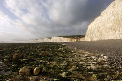 Seven Sisters, UK. White cliffs on rocky shore, blue sky and clouds, Seven Sisters, South Coast, UK Stock Photo