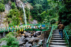 Seven Sisters Water Falls, Menrong Gong, North Sikkim. A tourist climbing through a small footbridge crosses over the stream to give the clients a better view Stock Photos