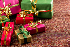 Seven Small Gifts on a Festive Blanket. Seven presents wrapped in green, magenta, red and gold. All with bows. Placed on a textured cloth. Plenty of text space Royalty Free Stock Photography
