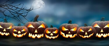 Free Seven Spooky Halloween Pumpkin, Jack O Lantern, With An Evil Face And Eyes On The Grass With A Misty Night Sky Background With A Stock Images - 196394974