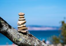 Cairn or Pile of Seven Stones Marking the Trails End. Seven stones balanced or piled on top of a tree limb setting on a bluff above a sandy beach with sand dunes royalty free stock photography