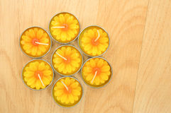 Seven sunflower candles align in hexagonal on the wood backgroun Royalty Free Stock Photos