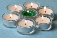 Seven tea lights. On light blue background Royalty Free Stock Image