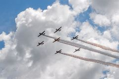 Seven AT-6 Texans Against Clouds With Smoke Trails Royalty Free Stock Photos