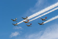 Seven AT-6 Texans in Cloudy Sky With Smoke Trails Royalty Free Stock Photo