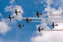 Seven AT-6 Texans Fly Overhead Trailing Smoke. EDEN PRAIRIE, MN - JULY 16 2016: Seven AT6 Texan airplanes fly overhead in cloudy sky with smoke trails at air Royalty Free Stock Photo