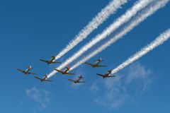 Seven AT-6 Texans Four Trailing Smoke. EDEN PRAIRIE, MN - JULY 16, 2016: AT6 Texan planes fly overhead with smoke trails from four planes at air show. The AT6 Stock Images