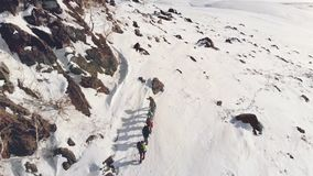 Seven travelers are in one line up to the peak of a snow covered hill, in a way it helps their gear and backpacks with. Supplies stock footage