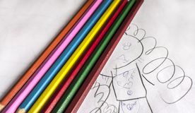 Seven colorful bright pencils lie on childish scribbles Stock Photography