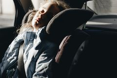 Seven-year charming girl sleeping in a children`s car seat stock photos