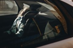 Seven-year charming girl sleeping in a children`s car seat royalty free stock image