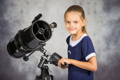 Seven-year girl adjusts the telescope and looked into the frame Royalty Free Stock Photo