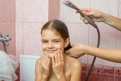 Seven-year girl bathe in a bath under shower Royalty Free Stock Photography