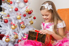Seven-year girl in beautiful dress is considering a gift sitting on the couch at Christmas tree Royalty Free Stock Photos